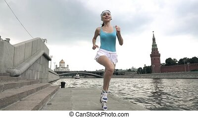 Athletic brunette girl runner against Moscow Kremlin, shot at 240 fps, slow motion steadicam clip