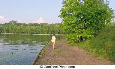 Athletic brunette girl running along riverside. Aerial shot