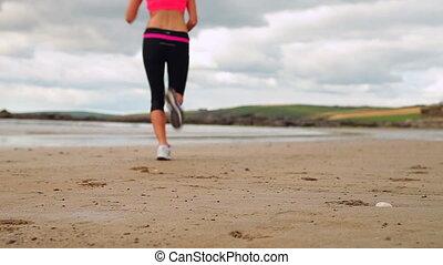 Athletic brunette running on the beach