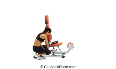 Athletic brunette woman on hydraulic exerciser. White...