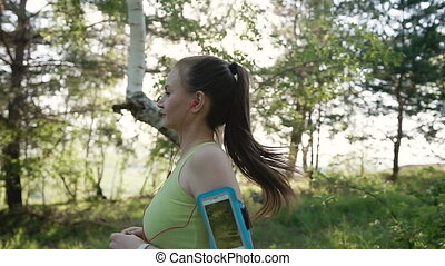 Athletic Caucasian young woman running and listening to music at headphone on smartphone at the outdoor in the forest at sunset. Athletic girl makes a jog in the park while listening to music