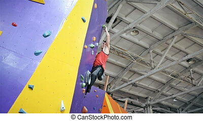 Athletic Climber Man Climbing On Practice Wall Indoors.