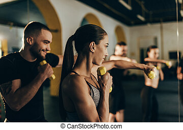 athletic couple exercising with dumbbells