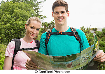 Athletic couple holding map on a hike