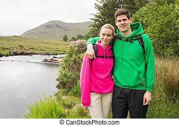 Athletic couple in hooded jumpers on a hike