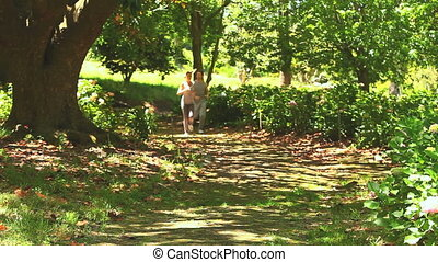 Athletic couple jogging in the wood - Athletic couple taking...