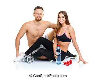 Athletic couple - man and woman after fitness exercise sitting w