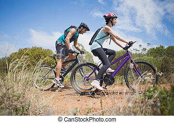 Athletic couple mountain biking - Side view of an athletic ...