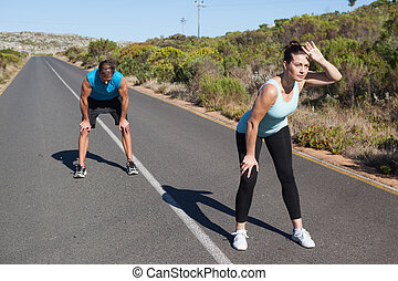 Athletic couple taking a break from jogging on the open road
