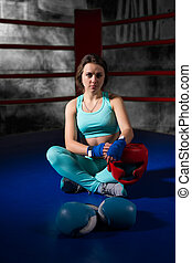 Athletic female boxer sitting near lying boxing gloves and helmet