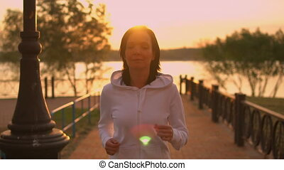 athletic female jogging at sunset