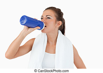Sporty female taking a sip of water after workout against a white background