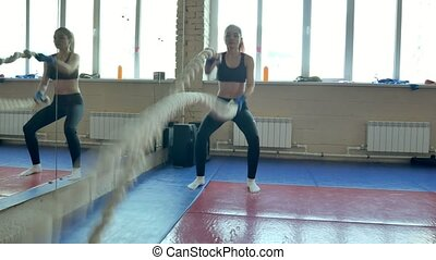 Athletic Female Working Out Using Battle Ropes....