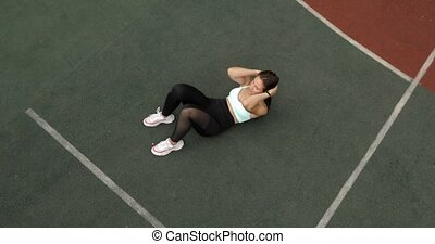 Athletic fit woman is doing abs exercises crunches on sport ground on stadium.