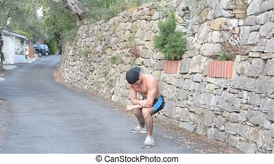Athletic, fit young man outdoor in country stretching