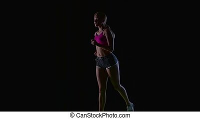 Athletic fitness woman running front view on a black background. Silhouette. Slow motion