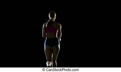 Athletic fitness woman running rear view on a black background. Silhouette