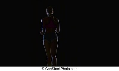 Athletic fitness woman running rear view on a black background. Silhouette. Slow motion