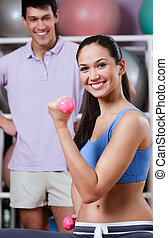 Athletic girl exercises in fitness gym with couch