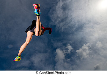 Athletic girl jumps while running in the mountains