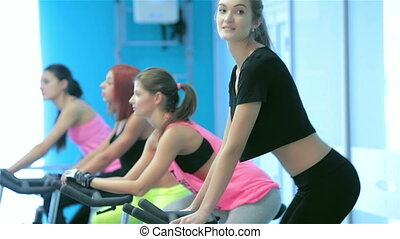 Athletic girl pedaling and looking at the camera on a stationary bike