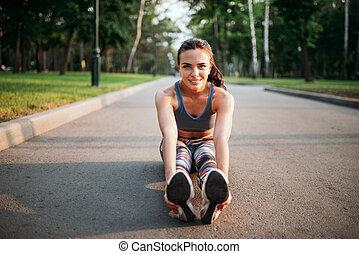 Athletic girl sitting on sidewalk in summer park - Athletic...