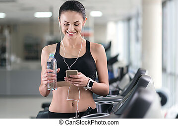 Athletic girl using smartphone in a gym