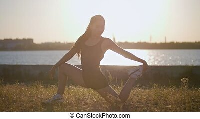 Athletic Girl With A Beautiful Figure Stretches Her Legs Before Running