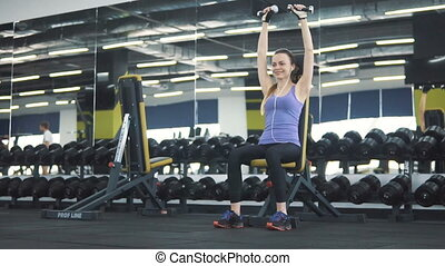 Athletic caucasian girl, in purple vest and black leggins, working out with small barbells at the gym