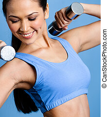 Athletic girl works out with dumbbells