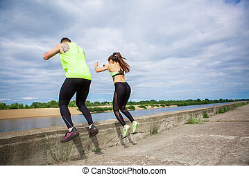 Athletic guy and girl fitness trainers synchronously jump. Healthy sport lifestyle. Photography for ad or blog. High quality photo