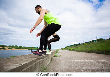Athletic guy and girl synchronously jump. Healthy sport lifestyle. Photography for ad or blog. High quality photo