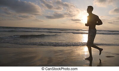 Athletic guy jogging along ocean shore during sunrise. Young sporty man running on the sea beach at sunset. Male sportsman exercising outdoor. Healthy active lifestyle. Workout at nature. Slow motion