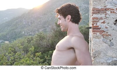 Athletic, handsome fit young man outdoor in country doing stretching exercises