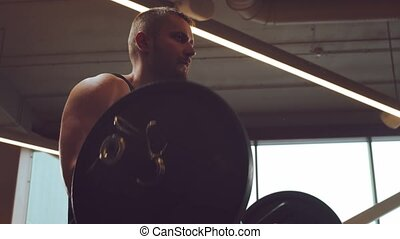 Athletic handsome male sportsman working in the gym using barbell. Strong and healthy bodybuilder abdominal training exercises. Sport, fitness, workout and lifestyle.