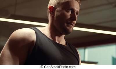 Athletic handsome male sportsman working in the gym using ...