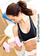 Athletic hispanic woman holding a dumbbell in her living-room