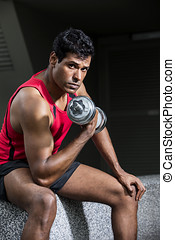 Athletic Indian man exercising with dumbbells - Muscular...