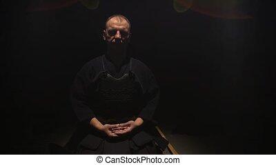 Athletic Kendo guru sitting on the floor with closed eyes. -...