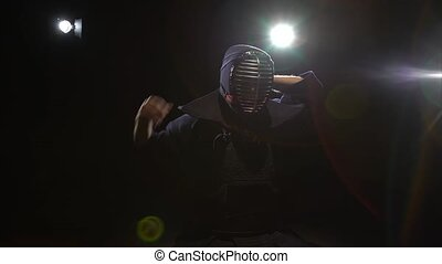Athletic Kendo warrior is putting on helmet and lacing it at...