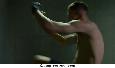 Athletic kick boxer working out throwing punches