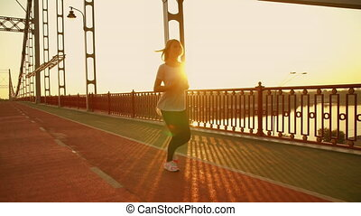 athletic lady runs in the morning - woman is having...