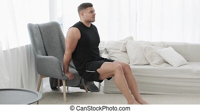 Athletic male exercising, camera in motion. Home fitness, training, workout, bodycare and wellness concept. Sportive young man is doing triceps exercise near armchair at home, side view.