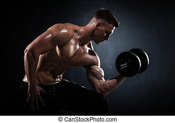Athletic male with dumbbells - Athletic shirtless young male...