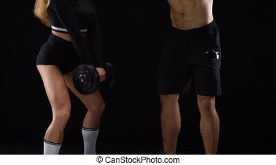 Athletic man and woman crouch with extra weight, training their legs and buttocks on a black background in studio. Muscular strong bodies