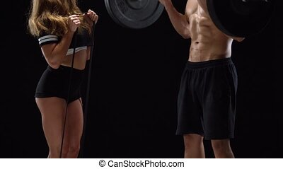 Athletic man and woman flexes their hands with dumbbells and...