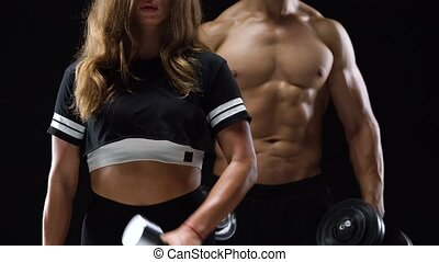 Athletic man and woman flexes their hands with dumbbells,...