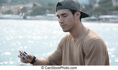 Athletic man at the seaside taking selfie with action camera