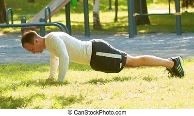 Athletic man bodybuilder doing a push-ups on the grass