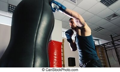 Athletic man boxing. Strong hits the punching bag